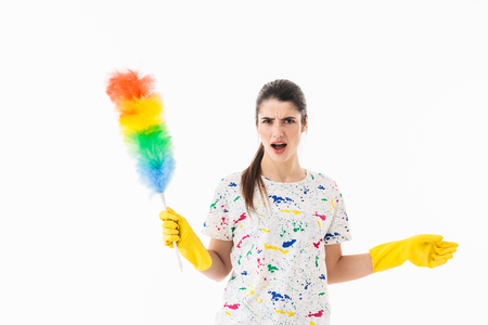 Photo of displeased housewife 20s wearing yellow rubber gloves for hands protection holding colorful duster while cleaning room isolated over white background