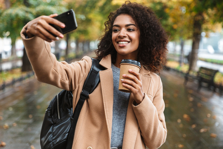 Beautiful young african woman wearing coat walking outdoors at the park, carrying backpack, taking a selfie