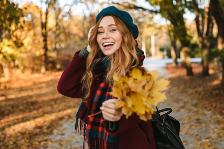 Cheerful young girl with long brown hair wearing autumn coat, walking at the park Banque d'images