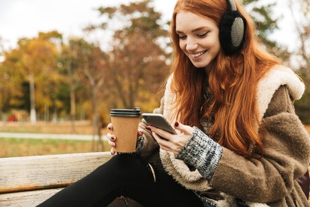 Lovely redheaded young girl listening to music with headphones while sitting on a bench, using mobile phone Stock Photo