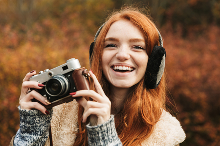 Lovely redheaded young girl listening to music, holding photo camera while standing outdoors