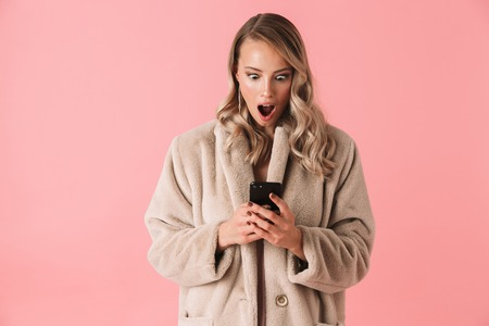 Shocked blonde woman wearing in fur coat using smartphone with open mouth over pink background