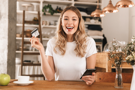 Portrait of european blond woman 20s wearing casual t-shirt using smartphone and plastic credit card while sitting in cozy cafe indoor 写真素材