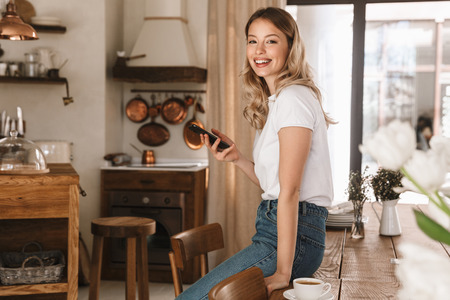 Portrait of european blond woman 20s wearing casual t-shirt using smartphone while standing in stylish wooden kitchen at home