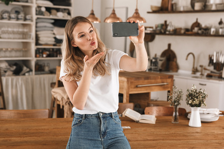 Portrait of pleased blond woman 20s wearing casual t-shirt taking selfie photo on smartphone while standing in stylish wooden kitchen at home 写真素材