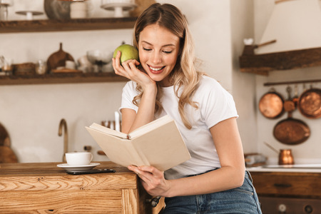 Portrait of relaxed blond woman 20s wearing casual t-shirt reading book and eating green apple while standing in stylish wooden kitchen at home