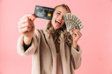 Cheerful blonde woman wearing in fur coat having fun with credit card and money over pink background