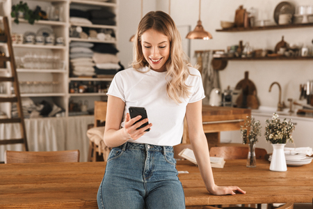 Portrait of charming blond woman 20s wearing casual t-shirt using smartphone while standing in stylish wooden kitchen at home