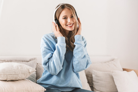 Portrait of happy blond girl 20s wearing headphones smiling and listening to music while sitting on sofa at home