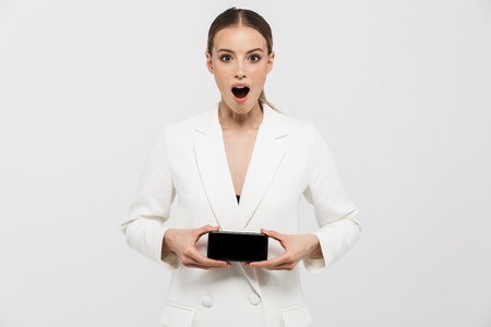 Photo of emotional businesswoman 20s wearing elegant jacket holding and showing on cell phone screen isolated over white background 版權商用圖片