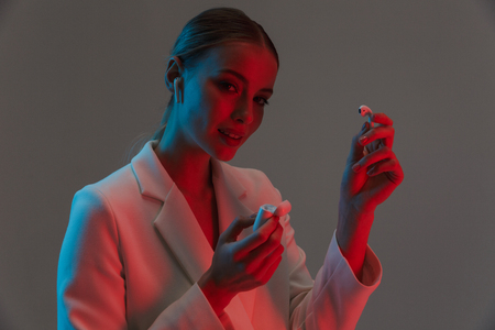 Image closeup of european woman 20s holding and wearing earpods while standing under neon lights isolated over gray background 版權商用圖片