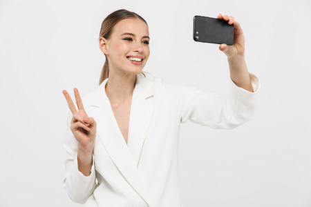 Photo of pleased businesswoman 20s wearing elegant jacket holding cell phone and taking selfie photo isolated over white background