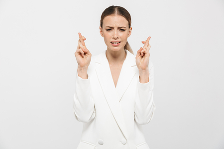 Photo of concentrated businesswoman 20s wearing elegant jacket wishing luck with keeping fingers crossed isolated over white background