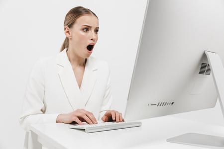Afbeelding van een geschokte mooie geweldige vrouw die geïsoleerd zit over een witte muurachtergrond met behulp van pc-computer. Stockfoto