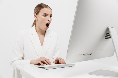 Bild einer schockierten schönen erstaunlichen Frau, die isoliert über weißem Wandhintergrund mit PC-Computer sitzt. Standard-Bild