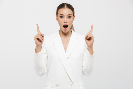 Photo of successful businesswoman 20s wearing elegant jacket pointing fingers upward at copyspace with surprise isolated over white background 免版税图像