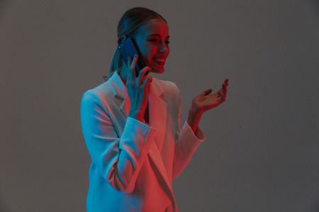 Image closeup of adorable woman 20s with ponytail hairstyle holding and talking on mobile phone while standing under neon lights isolated over gray background