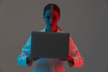 Image closeup of beautiful woman 20s holding and working on laptop while standing under neon lights isolated over gray background 스톡 콘텐츠