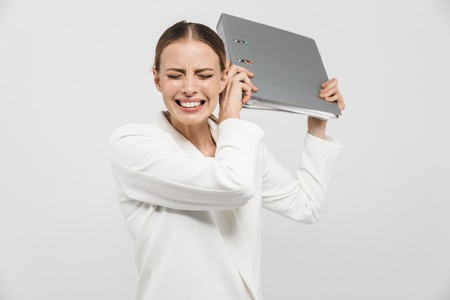 Image of a beautiful displeased nervous woman posing isolated over white wall background holding folder. Stockfoto - 122704588