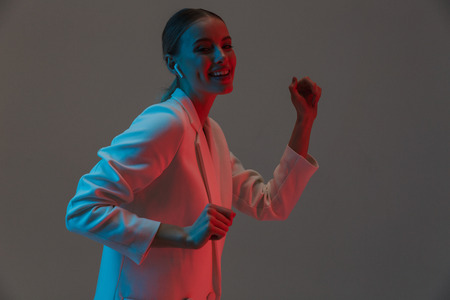 Photo closeup of cheery woman 20s wearing earpods listening to music and dancing while standing under neon lights isolated over gray background