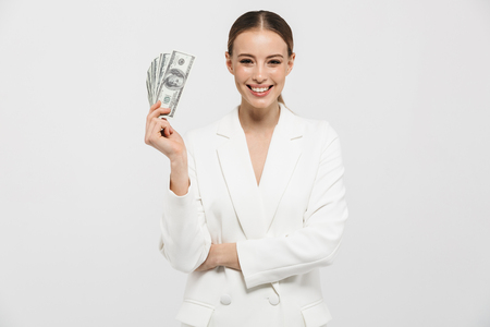 Photo of successful businesswoman 20s wearing elegant jacket holding fan with dollar money banknotes isolated over white background Imagens - 122704592