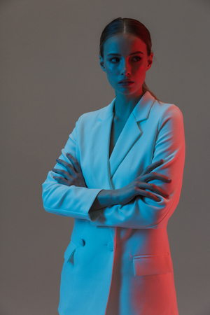 Photo of pleased woman 20s wearing elegant jacket looking at camera and standing under neon lights isolated over gray background
