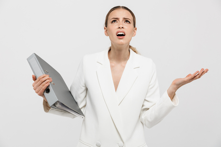 Image of a beautiful displeased nervous woman posing isolated over white wall background holding folder.
