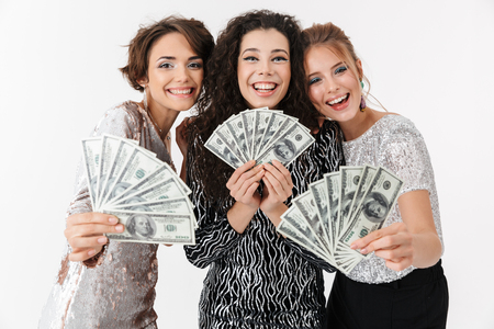 Pleased Three beauty women wearing in shiny clothes holding money and looking at the camera over grey background Stock Photo