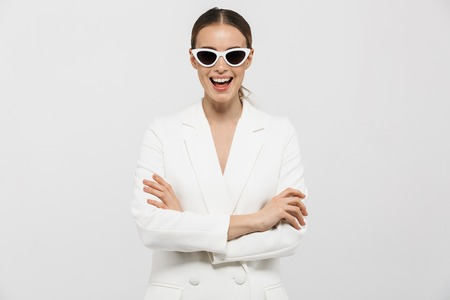Image of a beautiful happy woman posing isolated over white wall background wearing sunglasses.