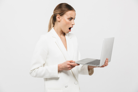 Image of a beautiful shocked excited amazing woman posing isolated over white wall background using laptop computer. 版權商用圖片