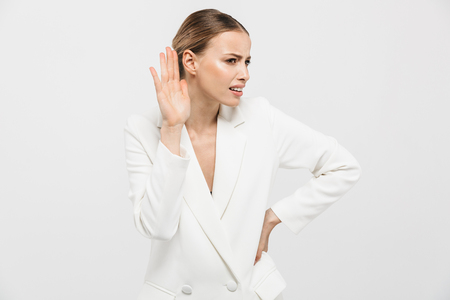 Image of a beautiful confused concentrated woman posing isolated over white wall background try to hear you.