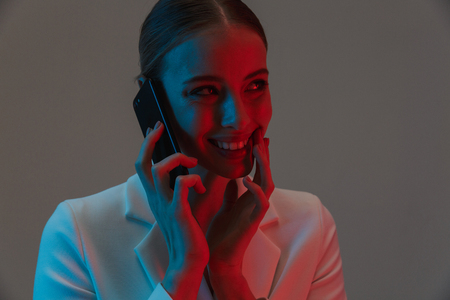 Image closeup of european woman 20s with ponytail hairstyle holding and talking on mobile phone while standing under neon lights isolated over gray background 版權商用圖片