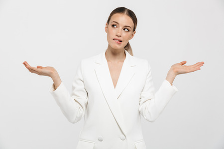 Photo of young businesswoman 20s wearing elegant jacket shrugging and throwing up hands isolated over white background