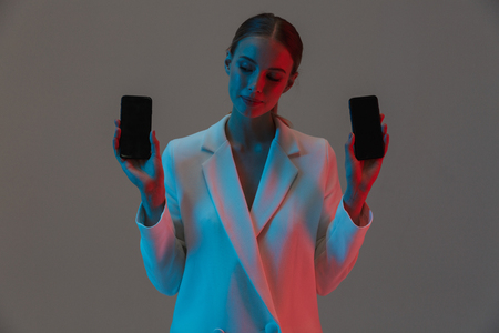 Image closeup of fashionable woman 20s holding two mobile phones and showing black screens while standing under neon lights isolated over gray background