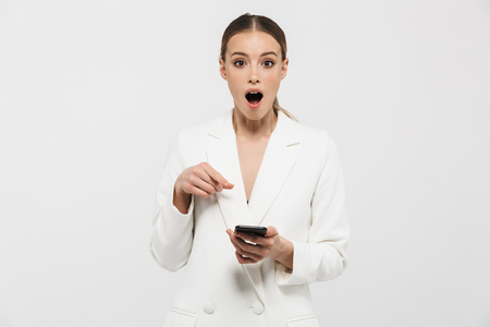 Photo of excited businesswoman 20s wearing elegant jacket holding and showing on cell phone screen isolated over white background