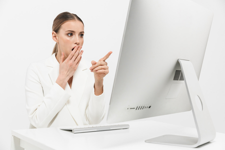 Image of a shocked beautiful amazing woman sitting isolated over white wall background using pc computer. Stock Photo