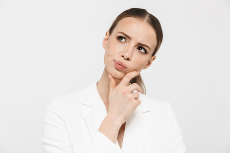 Photo of attractive businesswoman 20s wearing elegant jacket thinking and looking aside with puzzlement isolated over white background