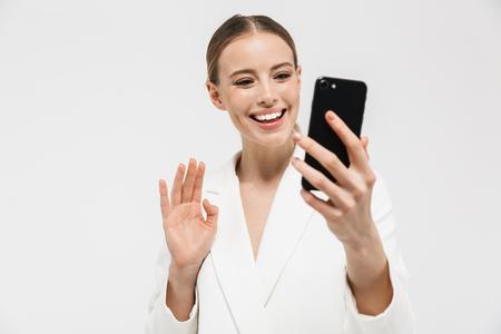 Foto di una donna d'affari europea di 20 anni che indossa una giacca elegante che tiene in mano un telefono cellulare e scatta una foto selfie isolata su sfondo bianco