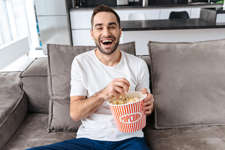 Photo of unshaved man 30s in casual t-shirt holding popcorn bucket and remote control while sitting on couch in living room Imagens