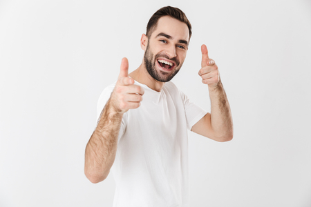 Handsome cheerful man wearing blank t-shirt standing isolated over white background, pointing at camera