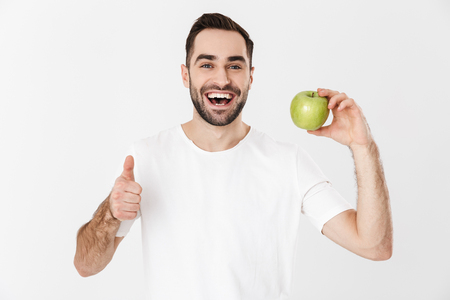 Handsome cheerful man wearing blank t-shirt standing isolated over white background, showing green apple, thumbs up