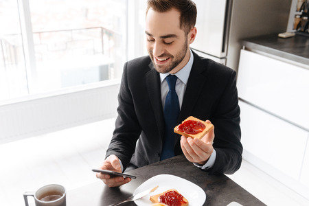 Image of smiling businessman 30s in formal suit having breakfast while using smartphone and working on laptop in bright apartment