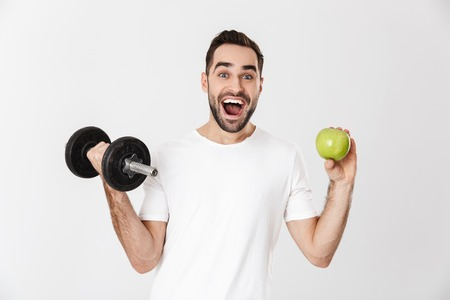 Handsome cheerful man wearing blank t-shirt standing isolated over white background, showing green apple, exercising with dumbbell