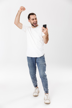 Full length of a handsome cheerful man wearing blank t-shirt standing isolated over white background, using mobile phone, celebrating Stock Photo
