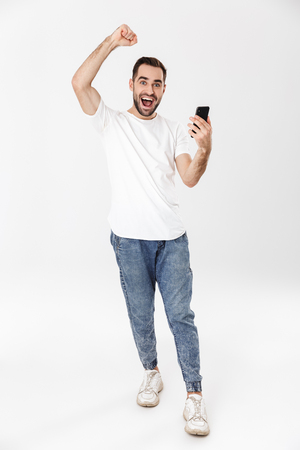 Full length of a handsome cheerful man wearing blank t-shirt standing isolated over white background, using mobile phone, celebrating Foto de archivo
