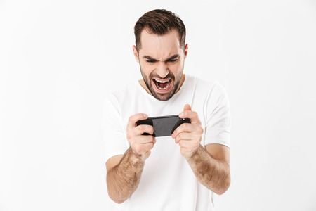Handsome angry man wearing blank t-shirt standing isolated over white background, playing games on mobile phone