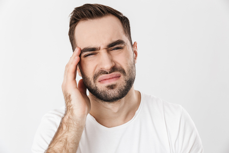 Upset man wearing blank t-shirt standing isolated over white background, suffering from a strong migraine Stock Photo