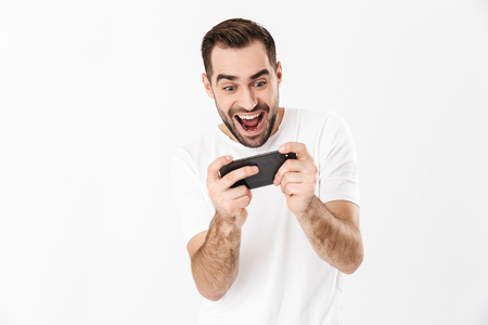 Handsome cheerful man wearing blank t-shirt standing isolated over white background, playing games on mobile phone
