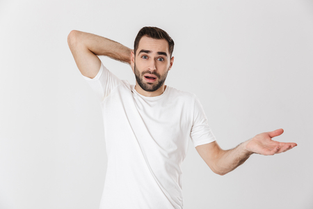 Confused man wearing blank t-shirt standing isolated over white background, screaming