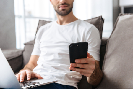 Photo of serious guy 30s in casual t-shirt holding smartphone and using silver laptop while sitting on sofa in bright apartment